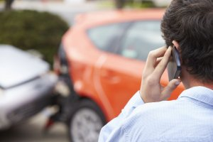 teenage driver making phone call to car accident attorney after traffic accident, car accident in the background, what to do after a minor car accident