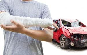 injured man holding his wrapped arm in front of a car totaled from a car accident, wondering what to do after a car accident